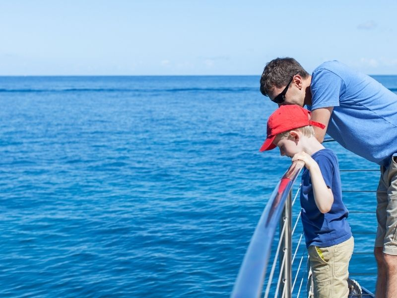 boy and man looking over a boat into water