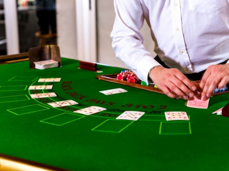 dealer dealing cards at casino table