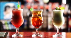 three cocktail drinks on a bar