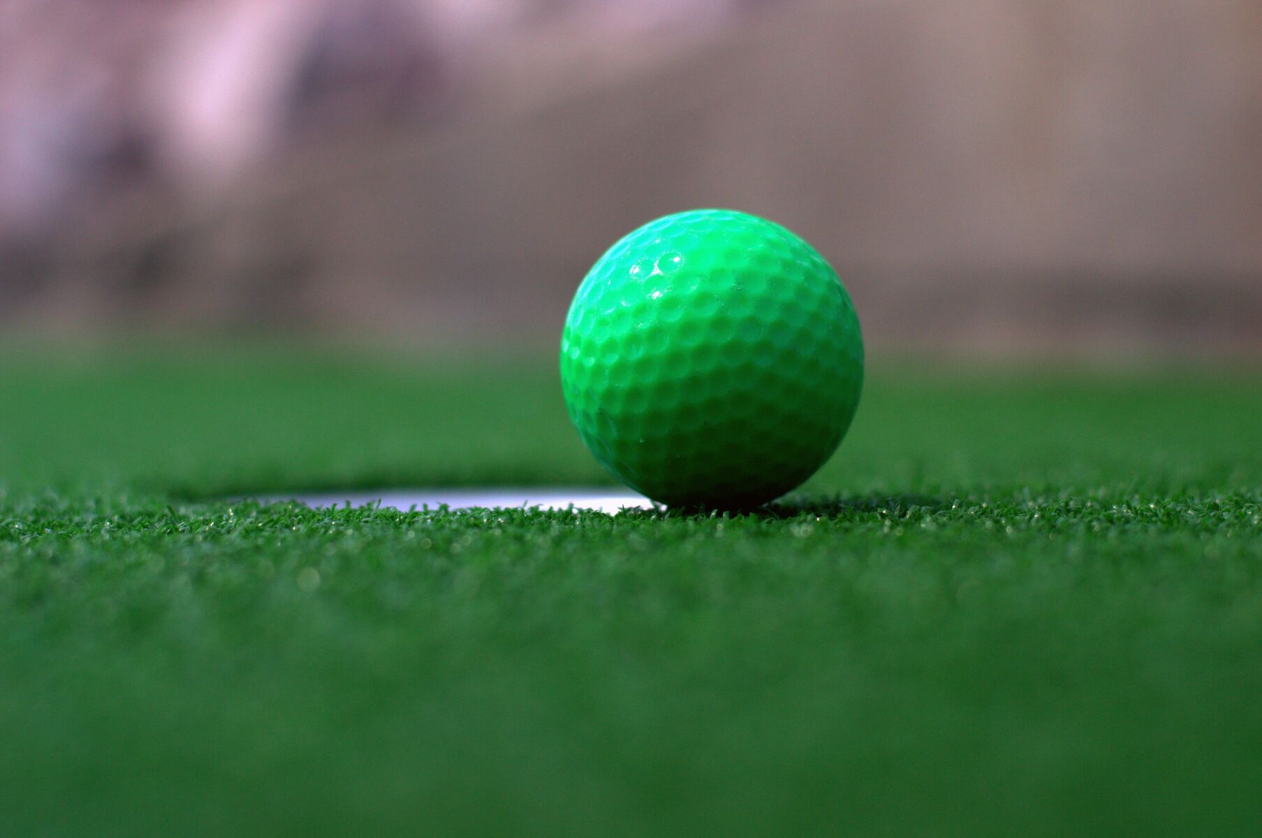 green golf ball by golf hole
